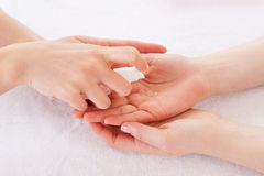 Applying antiseptic. Close-up of manicure master spraying antiseptic on female palm Stock Photography