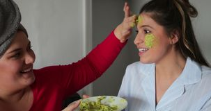 Applying an Avocado Facemask. Close-up of a small group of female friends sitting indoors enjoying a girls night in, they are applying an avocado mask to a young stock footage