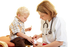 Applying a bandaid. Boy with scratched knee at the pediatrist royalty free stock photos