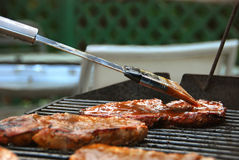 Applying BBQ Sauce to Steak on a Grill. Barbeque sauce is applied to steaks on an outdoor grill Royalty Free Stock Photo