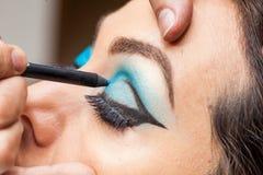Applying blue eyeshadow on white woman eyes Stock Photo