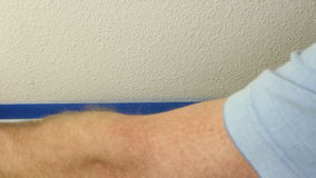 Applying Blue Painter's Tape. Male hand preparing for painting lower wall trim by placing blue painter's tape on the wall above it for protection when he does stock video