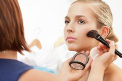 Applying blush on cheeks with blush brush Stock Photos