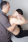 Applying cervical manipulation. Physical therapist applying cervical manipulation Royalty Free Stock Images