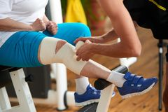 Applying a compression wrap for a sprained muscle. Mature women with sports injury gets first aid from fitness trainer in gym royalty free stock image