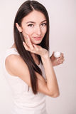 Applying cosmetic cream. A beautiful young woman applying face moisturizer. Scine care of the face and hands Stock Image