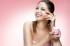Applying cosmetic cream on face Royalty Free Stock Image