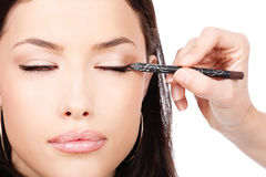 Applying cosmetic pencil on closed eye Royalty Free Stock Photos