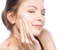 Applying cream for face. Attractive woman applying face cream isolated on white Royalty Free Stock Image