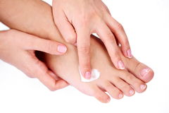 Applying cream on a foot by hand Stock Photography