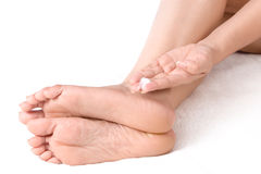 Applying cream to feet Stock Images
