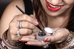 Applying eye liner. Closeup shot of female model with eye liner bottle stock image