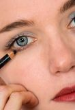 Applying eye liner - makeup series Royalty Free Stock Photos