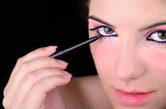 Applying Eye Makeup. Young girl applying eye liner makeup Royalty Free Stock Photo