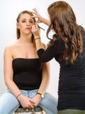 Applying eye makeup on beautiful model Stock Photos