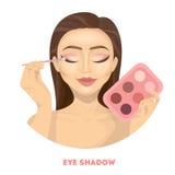 Applying eye shadow. Woman does make up Stock Photos