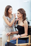 Applying eyebrow make-up stock photography