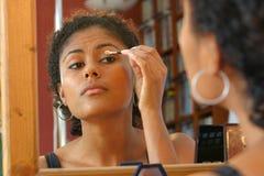 Applying eyeshadow. Beautiful brazilian woman applying eyeshadow Royalty Free Stock Photography