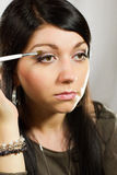 Applying eyeshadow using eyeshadow brush Royalty Free Stock Images
