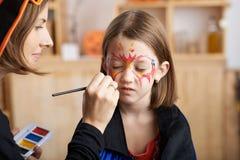 Applying face paint Stock Photos
