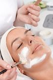 Applying facial cream by brush. Beautician applying facial cream on womans face, woman laying eyes closed with headband Royalty Free Stock Images