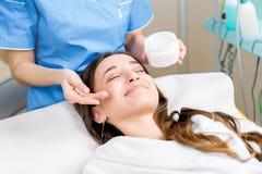 Applying facial cream. Cosmetologist applying facial cream to the client in the cosmetology office Stock Photo