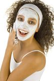Applying facial mask. Young happy woman with white purifying mask. She's looking at camera. She's on white background Stock Photos
