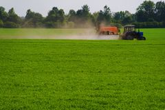 Applying fertilizer. (agriculture machine on green grass stock photography