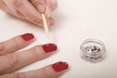 Applying finger nail gems Royalty Free Stock Photo