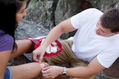 Applying first aid. A young men putting a band aid on a young women on a hike Royalty Free Stock Photos