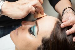 Applying foundation using a sponge to a white woma Stock Images
