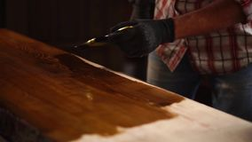 Applying fresh varnish on a wooden table. Experienced carpenter is applying fresh varnish on a grinded wooden table in a workshop. Applying all over the surface stock video footage
