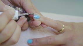 Applying Glitter On Blue Female Fingernail. Woman`s Hands Applying Glitter On Blue Female Fingernail In Slow Motion. Close Up Shot stock video