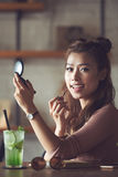 Applying gloss. Lovely young Asian woman with compact mirror applying lip gloss Stock Images