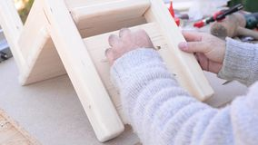 Applying glue on a little wooden chair stock video footage