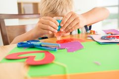 Applying glue. Kid applying glue to the colored paper to make a greeting card Royalty Free Stock Image