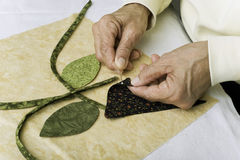 Applying glue to fabric. A quilter applies a dab of fabric glue to the back of fabric for applique to the background foundation Royalty Free Stock Photos