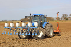 Applying granular pesticide and cultivating. A blue tractor applying granular pesticide and cultivating in springtime Royalty Free Stock Photo