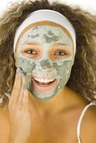 Applying green mask. Young woman putting on face green purifing mask. She's on white background. She's looking at camera Royalty Free Stock Images