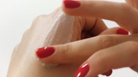 Applying hand cream, skin care on a white background