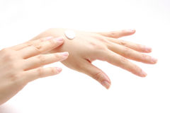 Applying hand cream to hands Stock Image