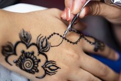 Applying henna tattoo. Woman painting black henna tattoo on a girl`s hand royalty free stock images