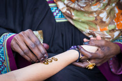 Applying henna for a temporary tattoo Stock Photos