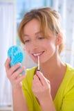Applying lip gloss Stock Images