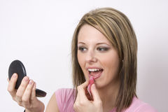 Applying Lip Gloss. Looking at her compact, a pretty young woman applies pink lip gloss Royalty Free Stock Photography