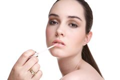 Applying lip gloss Royalty Free Stock Photography