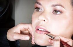 Applying lipstick. Make-up artist applying lipstick to young woman?s lips Stock Photo