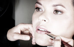 Applying lipstick. Make-up artist applying lipstick to young woman's lips - colour sepia Stock Images