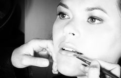 Applying lipstick. Make-up artist applying lipstick to young woman?s lips - black and white Royalty Free Stock Images
