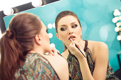 Applying lipstick with a brush Royalty Free Stock Image